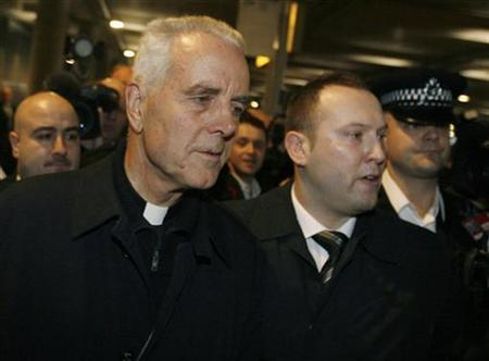 British-born Roman Catholic Bishop Richard Williamson (2nd L) is escorted by police on his arrival at Heathrow Airport in London February 25, 2009. REUTERS/Luke MacGregor