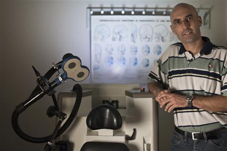 Neuronix CEO Eyal Baror poses for a photo next to a newly-developed device to treat Alzheimer's disease at Assaf Harofeh Medical Center near Tel Aviv October 24, 2012. REUTERS/Nir Elias