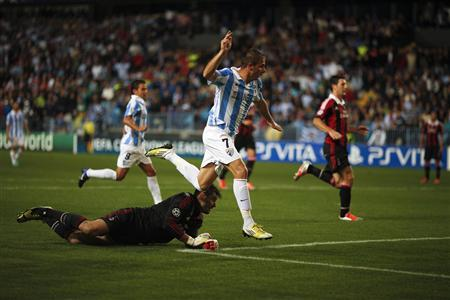 Malaga's Joaquin Sanchez (C) scores past AC Milan's goalkeeper Marco Amelia (bottom) during their Champions League Group C match at La Rosaleda stadium in Malaga, southern Spain October 24, 2012. REUTERS/Jon Nazca