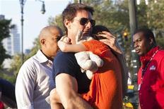 Ator Tom Cruise é visto carregando sua filha, Suri, em Nova York, em julho. Cruise abriu nesta quarta-feira um processo judicial por difamação no qual pleiteia 50 milhões de dólares de revistas que o acusaram de ter abandonado sua filha, Suri, de 6 anos, depois de se divorciar da atriz Katie Holmes. 11/07/2012 REUTERS/Andrew Burton