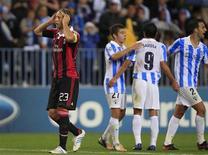 Massimo Ambrosini, do Milan, caminha enquanto jogadores do Málaga comemoram vitória pela Liga dos Campeões nesta quarta-feira. REUTERS/Marcelo del Pozo