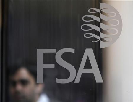 A man is seen behind the entrance door of the offices of the Financial Services Authority (FSA) in Canary Wharf, London, November 19, 2010. REUTERS/Simon Newman