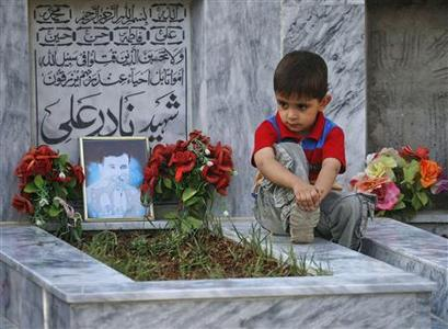Five-year old Sahil Hazara sits on the grave of his brother Nadir Ali, who was killed by unidentified gunmen, at the Hazara graveyard in Mehrabad in Quetta August 31, 2012. REUTERS/Naseer Ahmed