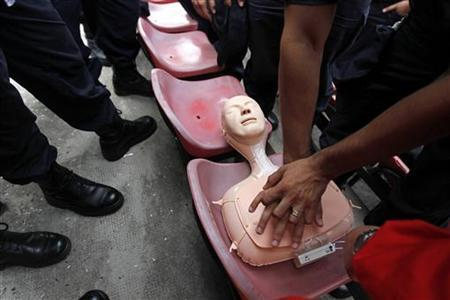 Police officers practice on a CPR training mannequin in Bucharest, Romania July 26, 2011. REUTERS/Bogdan Cristel