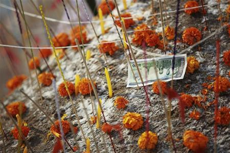 A banknote is left among flowers and candles on a sand stupa during ''Pi Mai Lao,'' or Lao New Year celebrations in Vientiane April 15, 2012. REUTERS/Stringer