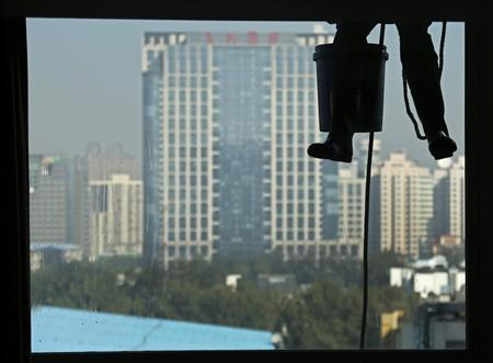 A worker cleans the window of an apartment building at a residential area in central Beijing, October 24, 2012. REUTERS/Petar Kujundzic