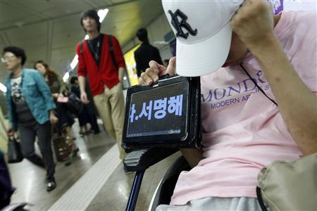 A disabled man on a wheelchair holds an iPad that shows the demands of the disabled attending a protest and holding a signature-seeking campaign at a subway station in Seoul in this September 21, 2012 picture. The Korean characters read ''(Please) sign your name (to show your support for us)''. The protest has lasted more than 60 days and aims to change South Korea's benefits system, which campaigners say humiliates disabled people by ''grading'' them according to their disability. Picture taken September 21, 2012. REUTERS/Kim Hong-Ji