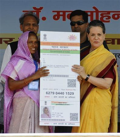 Chief of India's ruling Congress party Sonia Gandhi (R) presents the 210 millionth biometric card to Vali (L), a villager residing in the desert Indian state of Rajasthan, during the national launch of a scheme to make direct cash transfers to the poor, at Dudu town in Rajasthan October 20, 2012. Picture taken October 20, 2012. REUTERS/Vinay Joshi