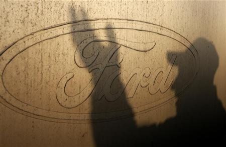 The shadow of a worker is seen on the logo of Ford Motor Co at the company's assembly plant after an emergency meeting with the plant management in Genk October 24, 2012. REUTERS/Francois Lenoir