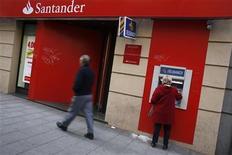 Женщина получает деньги из банкомата около отделения банка Santander в Мадриде, 16 октября 2012 года. Прибыль Santander, крупнейшего банка еврозоны, упала за девять месяцев на две трети из-за списаний, связанных с неудачными инвестициями в недвижимость во время десятилетнего жилищного бума в Испании. REUTERS/Susana Vera