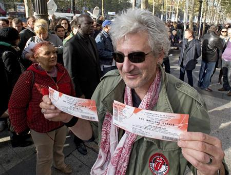 A Rolling Stones fan displays two tickets he purchased for a short warm-up gig in Paris October 25, 2012 as the group prepares for a series of 50th anniversary concerts later this year. REUTERS/Philippe Wojazer