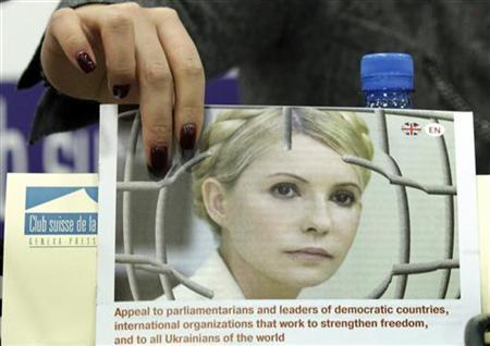 Yevgenia Tymoshenko, daughter of jailed former Ukrainian prime minister Yulia Tymoshenko, holds a portrait of her mother at the start of a conference at the Geneva Press Club in Geneva October 24, 2012. REUTERS/Denis Balibouse