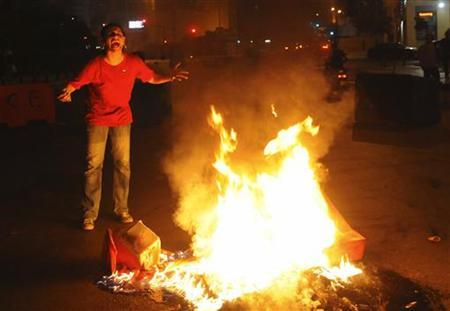A Sunni Muslim woman reacts as she burns a tire, blocking a street in Beirut during protests against the killing of senior intelligence official Wissam al-Hassan in an explosion, October 19, 2012. REUTERS/Hussam Shebaro