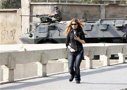 A woman runs for cover near a Lebanese army armoured personnel carrier (APC) during clashes between the army and Sunni Muslim gunmen in Beirut October 22, 2012, after a night of tension following the funeral of an intelligence official killed by a car bomb. REUTERS/Mohamed Azakir