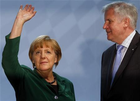 German Chancellor Angela Merkel waves next to Bavarian Prime Minister Horst Seehofer (R) before her guest speech at a Christian Social Union (CSU) party meeting in Munich October 19, 2012. REUTERS/Michael Dalder