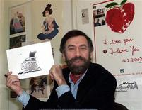 Syrian leading cartoonist Ali Farzat poses with one of his works at his workshop in Damascus on January 31, 2001.