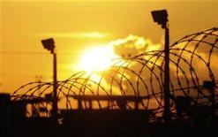 Солнце восходит над спецтюрьмой США в заливе Гуантанамо на Кубе 18 октября 2012 года. WikiLeaks начал публикацию материалов, которые называет подлинными документами Пентагона об условиях содержания в спецлагерях в Ираке и военной тюрьме Гуантанамо на Кубе, которую претендующий на второй срок президент США Барак Обама обещал закрыть еще в первый год правления. REUTERS/Michelle Shephard/Pool