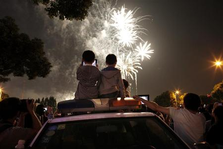Children sit on top of a police vehicle as they watch a fireworks display as part of China's Mid-Autumn festival in Shanghai, October 3, 2012. REUTERS/Carlos Barria