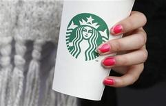 A woman holds a Starbucks takeaway cup in London October 24, 2012. Starbucks's reputation among consumers in Britain has been hit by wave of criticism of its tax affairs from politicians and the media, pollster YouGov said. REUTERS/Suzanne Plunkett