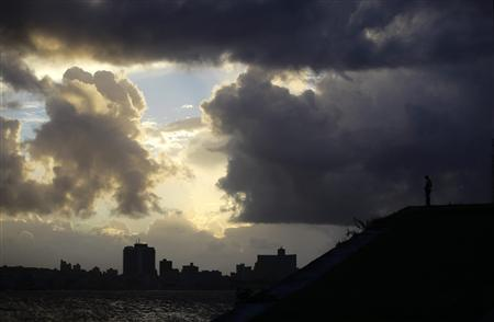 A man looks at the city as storm clouds fill the sky over Havana October 24, 2012. Hurricane Sandy battered Jamaica with ferocious winds, waves and rain on Wednesday, knocking down trees and power lines across the Caribbean country as it cut a path toward Cuba and the Bahamas. REUTERS/Desmond Boylan