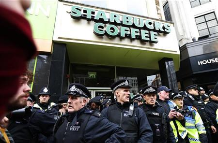 Police officer protect a Starbucks after demonstrators threatened to occupy it during a protest march organised by the Trades Union Congress (TUC), in Oxford Street, in central London October 20, 2012. REUTERS/Suzanne Plunkett