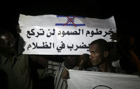Protesters hold banners and chant anti-Israel slogans as the Sudanese cabinet holds an emergency session over a factory blast, in Khartoum October 24, 2012. The banner reads ''Khartoum steadfastness won't kneel to treacherous hits in the dark''. REUTERS/Stringer