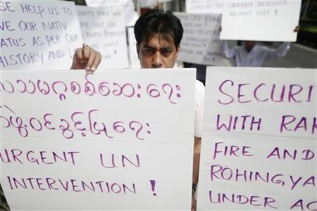 Men hold banners as they protest in front of the U.S. embassy in Bangkok October 24, 2012. REUTERS/Damir Sagolj