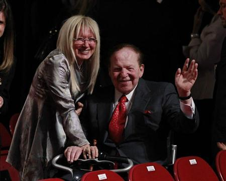 Chairman and CEO of the Las Vegas Sands casino Sheldon Adelson (C), a donor to Republican presidential nominee Mitt Romney, waves to photographers with his wife Miriam Ochsorn at the end of the first presidential debate between Romney and President Barack Obama in Denver October 3, 2012. REUTERS/Jason Reed