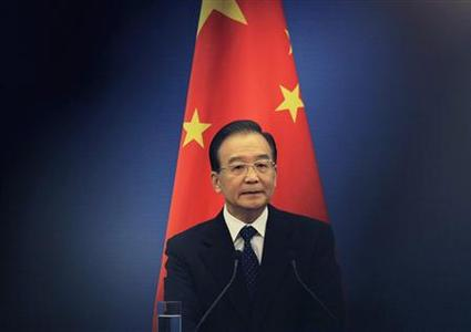 China's Premier Wen Jiabao stands in front of a Chinese national flag as he attends a joint news conference of the fifth trilateral summit among China, South Korea and Japan at the Great Hall of the People in Beijing, in this May 13, 2012 file photo. REUTERS/Petar Kujundzic/Files