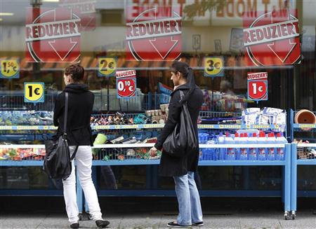 Women inspect a shop with reduced goods in the western city of Herne September 11, 2012. REUTERS/Ina Fassbender