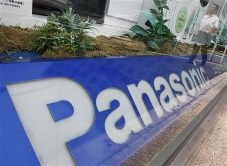 A pedestrian is reflected on a window displaying Panasonic Corp's products in Tokyo June 28, 2012. REUTERS/Yuriko Nakao