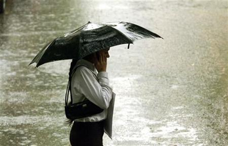 A pedestrian talks on her cellphone while using an umbrella in New Delhi June 21, 2003. REUTERS/B. Mathur/Files