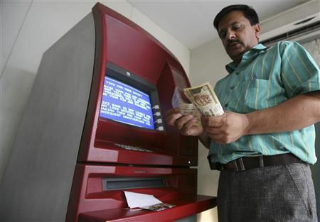 A man counts money after withdrawing it from an ATM in Jammu October 14, 2008. REUTERS/Amit Gupta/Files