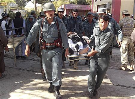Afghan policemen carry the body of a civilian after a bomb blast in Faryab province October 26, 2012. A suicide bomber killed at least 40 people in a mosque in Afghanistan's relatively peaceful north on Friday as worshippers gathered for prayers marking the Muslim Eid al-Adha holiday, police officials said. REUTERS/Stringer