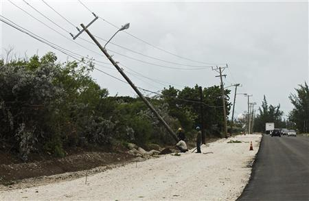 Workers repair a utility pole damaged by Hurricane Sandy in Kingston, October 25, 2012. REUTERS/Gilbert Bellamy