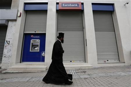 A Greek Orthodox priest walks past a closed Postbank branch during a 24-hour strike of bank employees in Athens October 24, 2012. REUTERS/Yorgos Karahalis