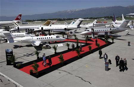 Visitors walk past an aircraft in the static display area during the Annual European Business Aviation Convention & Exhibition (EBACE) at Cointrin airport in Geneva May 14, 2012. REUTERS/Denis Balibouse