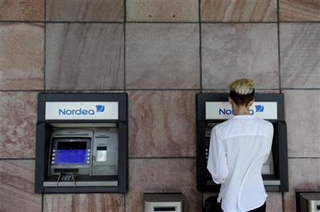 A customer makes a withdrawal from a Nordea automatic teller machine in Stockholm August 29, 2011. REUTERS/Jessica Gow/Scanpix