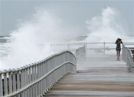 Jean Marie Brennan walks along the jetty at Lighthouse Point Park as Hurricane Sandy passes offshore in Ponce Inlet, Florida, October 26, 2012. REUTERS/Steve Nesius
