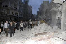 A crowd gathers in front of damaged buildings after a car bomb exploded at Daf al-Shok district, in Damascus October 26, 2012, in this handout photograph released by Syria's national news agency SANA. REUTERS/Sana