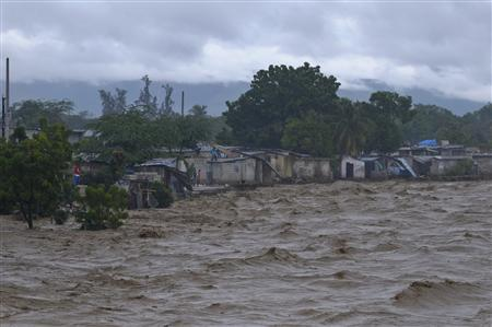 Heavy rains from Hurricane Sandy causes the Croix de Mission river to swell to levels that threaten to flood the homes along its bank in Port-au-Prince October 25, 2012. REUTERS-Swoan Parker