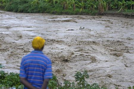 A man watches heavy rains from Hurricane Sandy cause the Croix de Mission river to swell to levels that threaten to flood the homes along its bank and nearby areas, in Port-au-Prince October 25, 2012. REUTERS-Swoan Parker