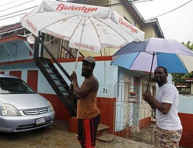 Jamaicans shelter themselves from the rain of approaching Hurricane Sandy in Kingston October 24, 2012. REUTERS-Gilbert Bellamy