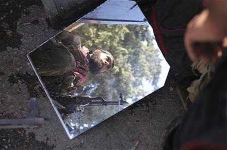 A member of the Free Syrian Army is reflected in a mirror in a house they use as a base in Haram town, Idlib Governorate, October 26, 2012. REUTERS/Asmaa Waguih