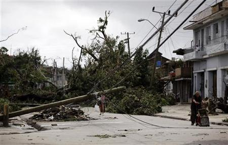 A man pushes a trolley beside fallen trees and power lines on a street in Santiago de Cuba October 26, 2012. REUTERS/Desmond Boylan