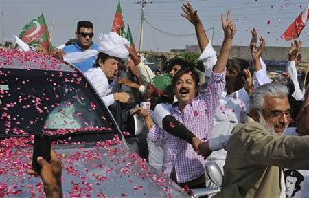 Imran Khan, cricketer-turned-politician and head of Pakistan Tehreek-e-Insaf (PTI), wears a traditional turban as his supporters shout slogans and throw rose petals as he leads a peace march against U.S. drone strikes from Islamabad to South Waziristan, in Musa Khel, located in the province of Punjab October 6, 2012. REUTERS/Saad Arsalan