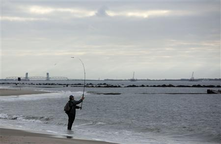 A fisherman casts his line before the arrival of Hurricane Sandy at Coney Island, New York, October 27, 2012. REUTERS-Chip East