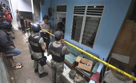 Troops from the Special Detachment 88 squad and a police officer stand guard outside the house of a suspected militant after a raid in Jakarta October 27, 2012. REUTERS/Jefri Tarigan