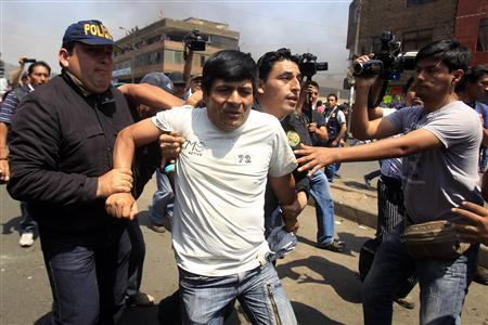 Policemen arrest a man during clashes between workers and residents living close to the La Parada wholesale market, and riot police officers, in Lima October 27, 2012. REUTERS/Enrique Castro-Mendivil
