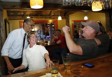President Barack Obama (L) mingles in the bar with diners at the Common Man restaurant in Merrimack, New Hampshire October 27, 2012. REUTERS/Jonathan Ernst